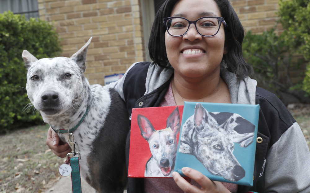 Danielle Moore poses for photos with Kana and also paintings of the pet Australian cattle dog in Dallas on March 2.