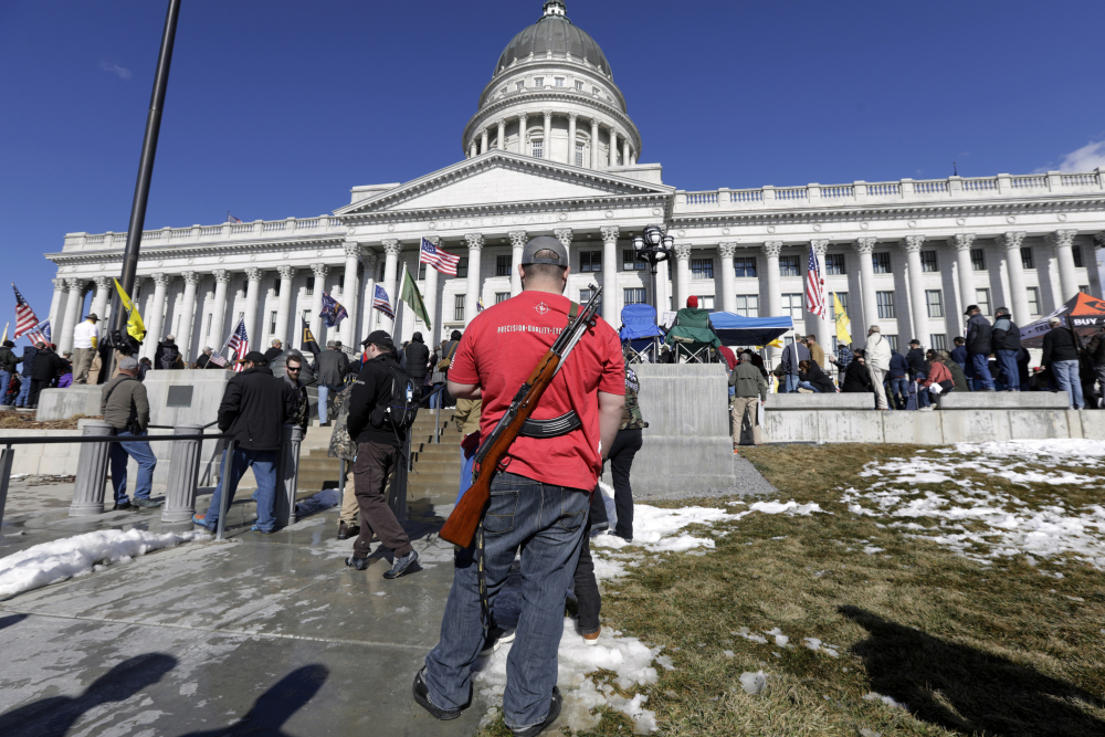 A man carries his weapon during a second amendment gun rally at the Utah State Capitol on Feb. 8, 2020, in Salt Lake City. Utah is one of several more states weighing proposals this year that would allow people to carry concealed guns without having to get a permit.