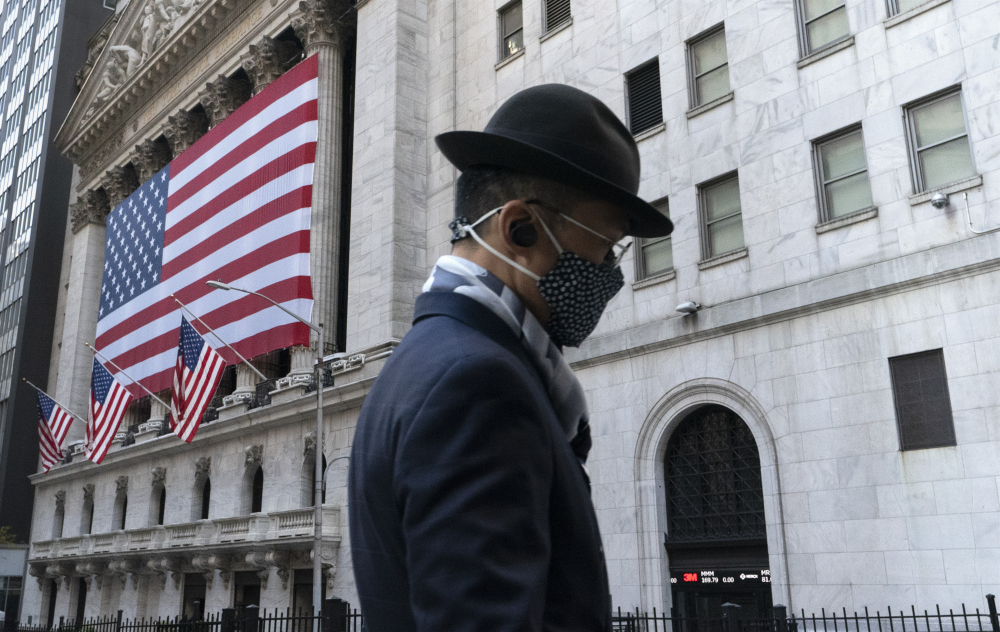 A man passes the New York Stock Exchange. U.S. stocks fell from their record highs on Monday. Rising virus cases, the emergence of a mutant variant and concerns that the rollout of the vaccine isn't happening fast enough are keeping investors on edge, said Adam Taback, chief investment officer for Wells Fargo Private Bank.