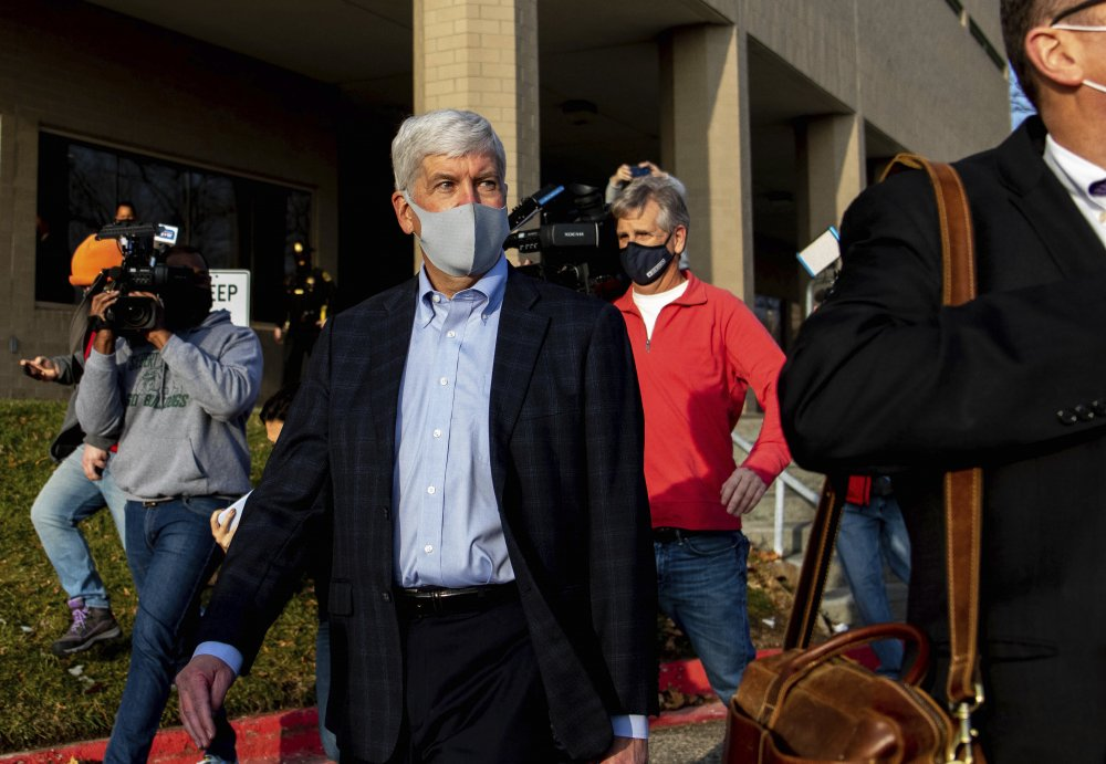 Former Gov. Rick Snyder walks past the media after his video arraignment on charges related to the Flint water crisis on Thursday outside the Genesee County Jail in downtown Flint.  Snyder pleaded not guilty to misdemeanor charges of willful neglect of duty in Flint.