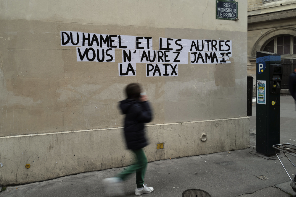 "A sign reads ""Duhamel, and the others, you will never be in peace,"" referring to prominent French political expert Olivier Duhamel, in Paris, on Tuesday."