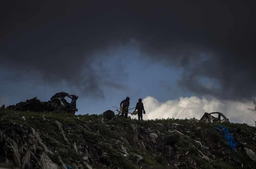 Two Palestinian boys play on top of piles of garbage on a rainy day in a poor neighborhood of Khan Younis, in the southern Gaza Strip, Wednesday, Jan. 20.