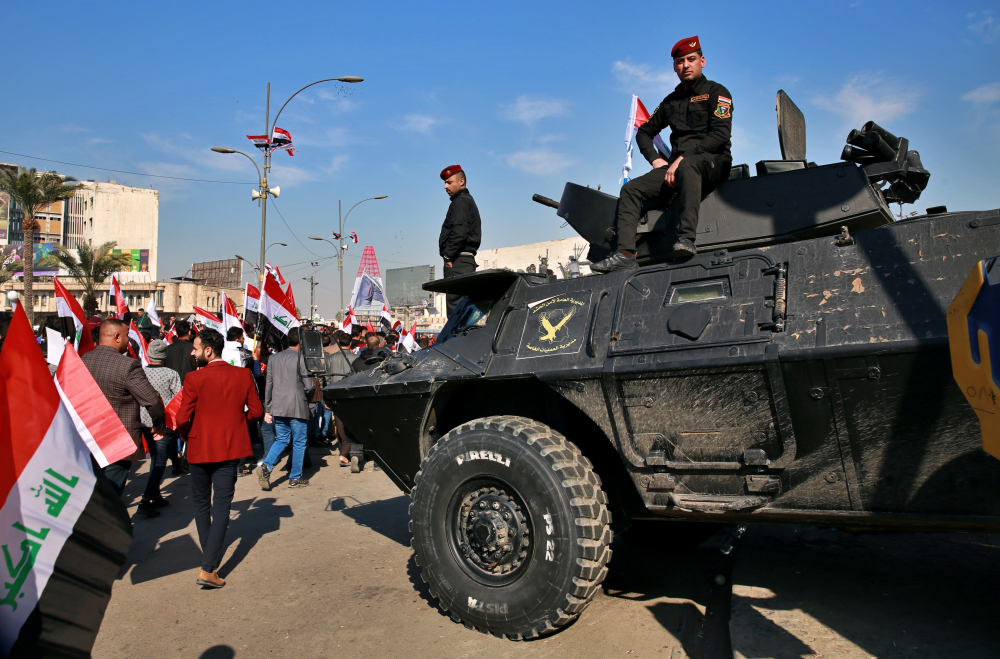 Security forces stand guard while supporters of Popular Mobilization Forces protest Sunday in Tahrir Square, Iraq. Thousands of Iraqis converged on a landmark central square in Baghdad on Sunday to commemorate the anniversary of the killing of Abu Mahdi al-Muhandis, deputy commander of the Popular Mobilization Forces, and General Qassem Soleimani, head of Iran's Quds force in a U.S. drone strike.