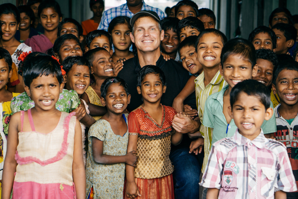 John Marshall looking at the camera surrounded by kids in Visakhapatnam, India.