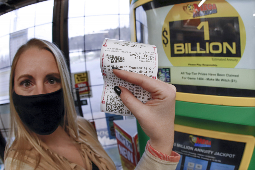 A patron, who did not want to give her name, shows the ticket she had just purchased for the Mega Millions lottery drawing at the vending kiosk in a Smoker Friendly store Friday in Cranberry Township, Pa.