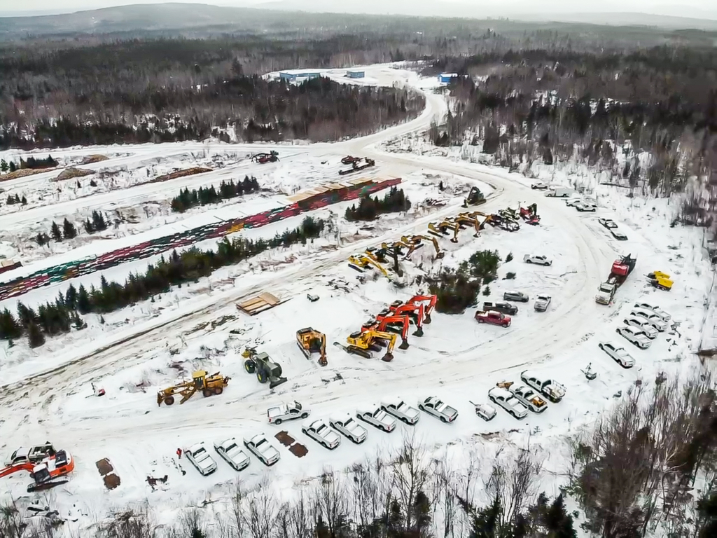 Wood-harvesting equipment, excavators and other machines that will be used to clear the corridor for the New England Clean Energy Connect project are arrayed Friday at the so-called Marshall Yard, off Route 201 near West Forks. At the rear, massive stacks of wooden erosion-control mats await transport into the forest.