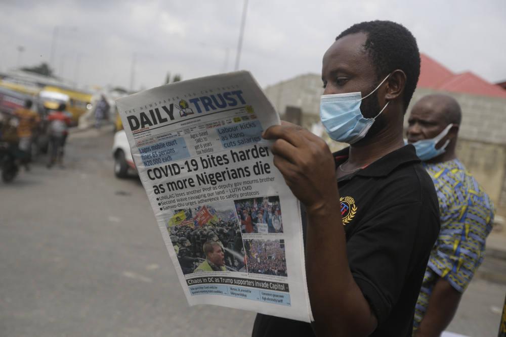 A man reads a newspaper reacting to the news of the assault on U.S Congress, on a street Thursday in Lagos, Nigeria. News reports show police with gun drawn as protesters try to break into the House Chamber at the U.S. Capitol on Wednesday in Washington.