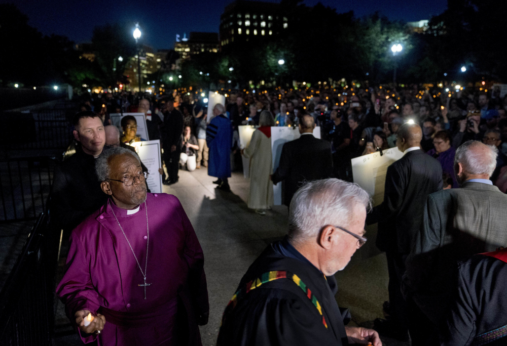 The Most Rev. Michael Curry, left, the presiding bishop of the U.S. Episcopal Church, and others take part in a candlelight vigil outside the White House in Washington in 2018.