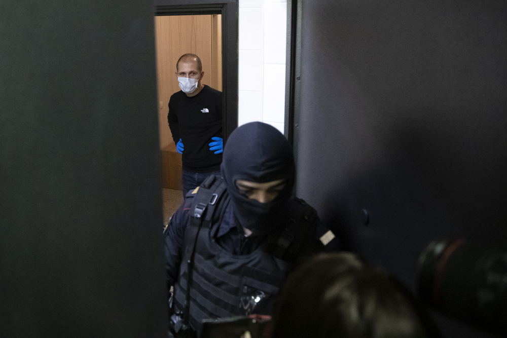 A police officer and an investigator stands behind the door of the apartment of jailed opposition leader Alexei Navalny on Wednesday in Moscow, Russia.