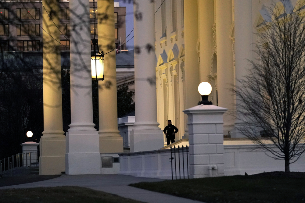A U.S. Secret Service guard stands at the North Portico of the White House after the U.S. House impeached President Trump in Washington on Wednesday. It isn't clear when Trump will leave the White ouse for good because he isn't adhering to any traditional protocols for the transition of power.