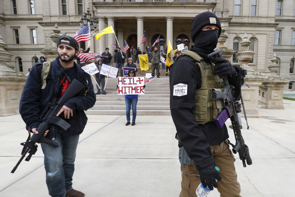 Protesters carry rifles near the steps of the Michigan State Capitol building on April 15 in Lansing, Mich.