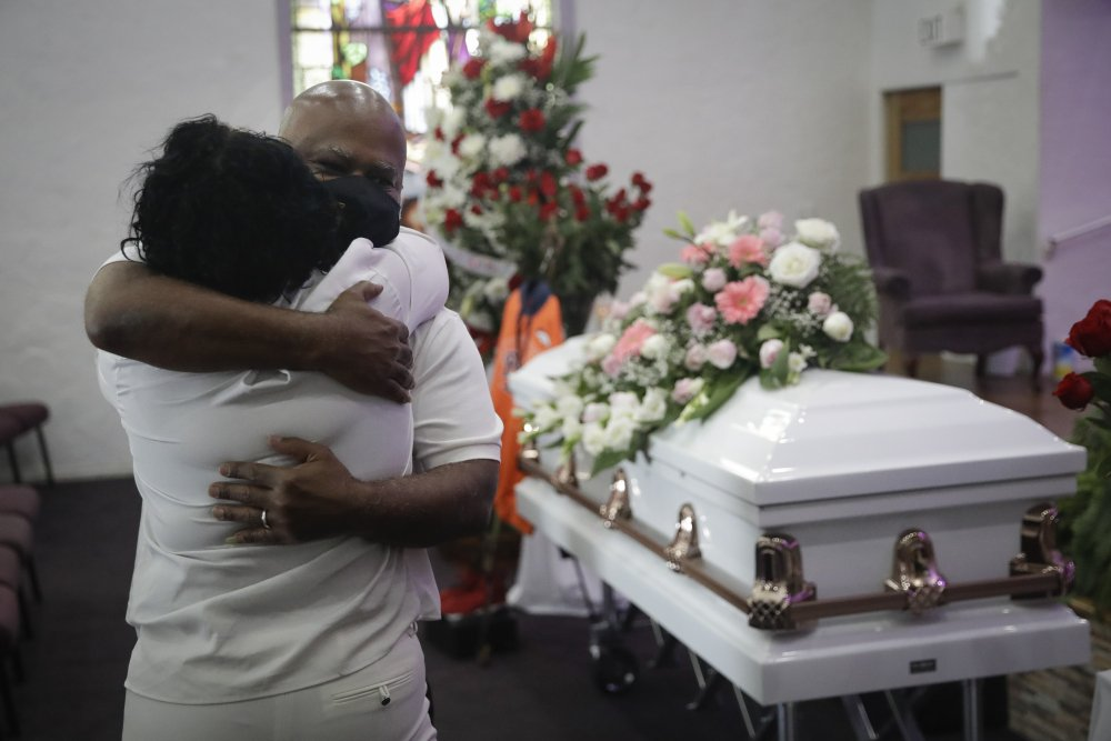 Darryl Hutchinson, facing camera, is hugged by a relative during a funeral service for Lydia Nunez, who was Hutchinson's cousin at the Metropolitan Baptist Church in Los Angeles.