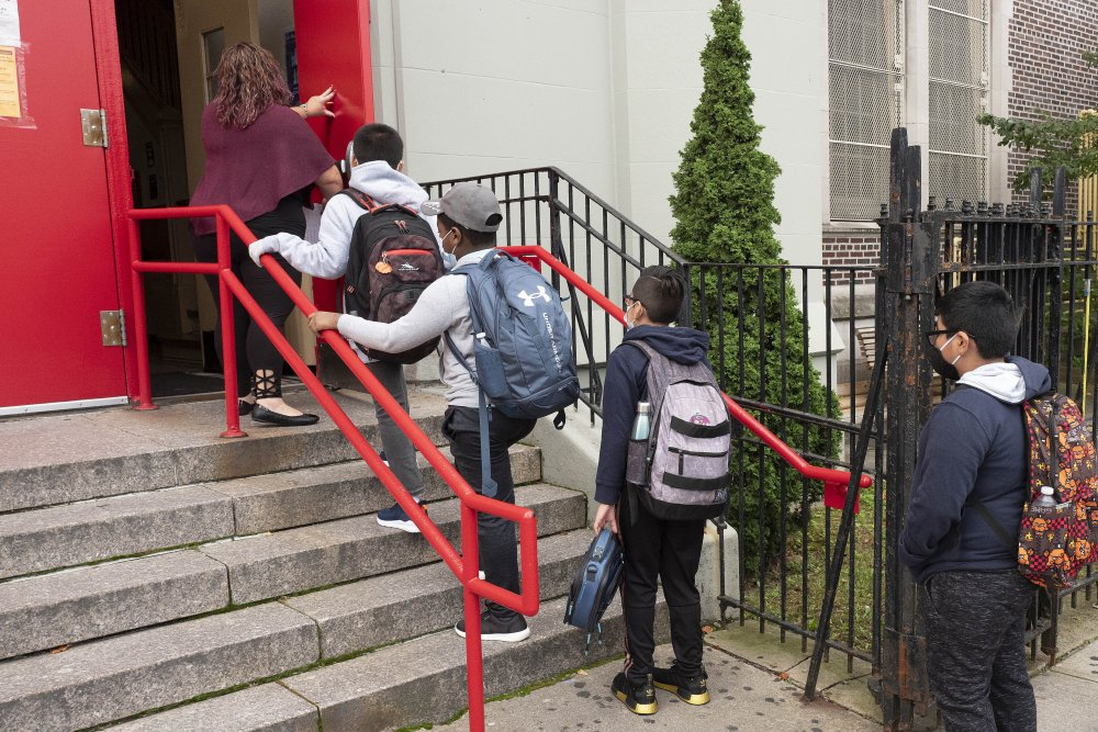 A teacher leads her students into an elementary school in the Brooklyn borough of New York in September 2020.