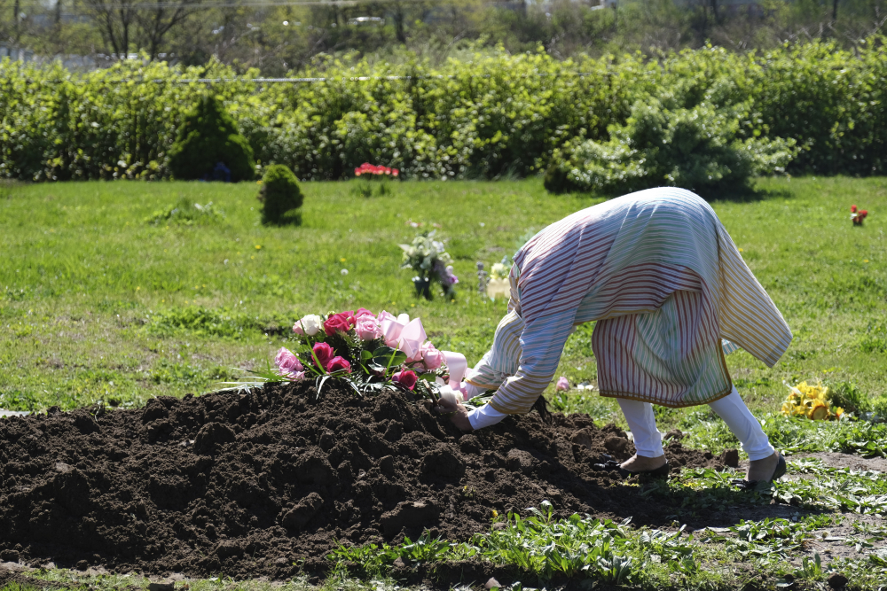 Erika Bermudez becomes emotional as she leans over the grave of her mother, Eudiana Smith, at Bayview Cemetery in Jersey City, N.J., on May 2. Bermudez was not allowed to approach the gravesite until cemetery workers had buried her mother, who died of COVID-19. Other members of the family and friends stayed in their cars.