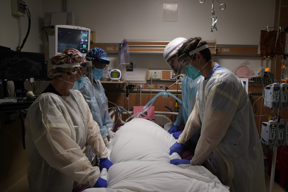 Medical workers prepare to manually prone a COVID-19 patient in an intensive care unit Dec. 22 at Providence Holy Cross Medical Center in the Mission Hills section of Los Angeles.