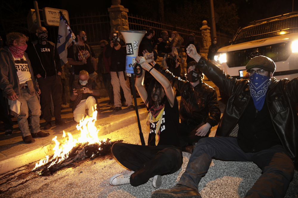 Israeli protesters block a road during a demonstration against Israeli Prime Minister Benjamin Netanyahu near his official residence in Jerusalem during the third nationwide coronavirus lockdown Saturday.