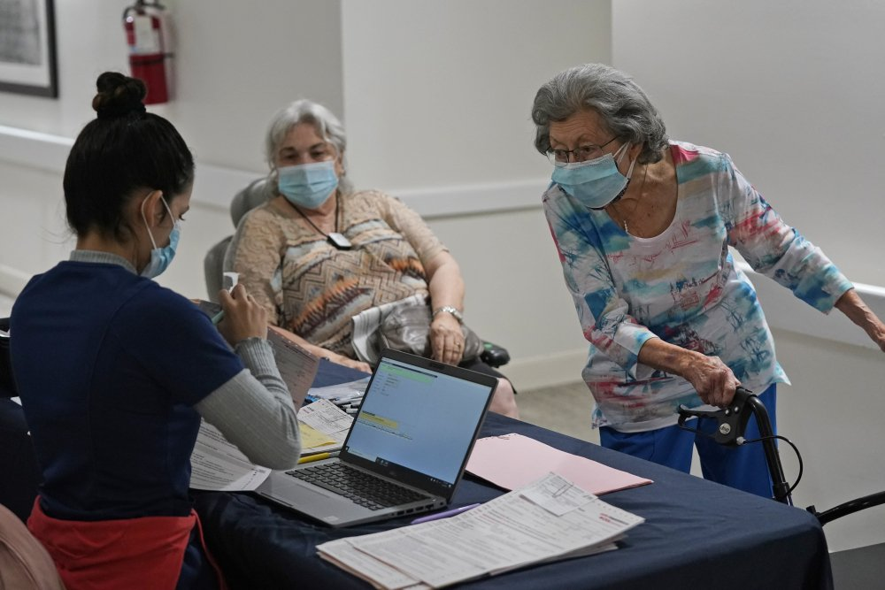 Mitzi Hansrote, right, 86, and Deanna Sutton, center, 83, check in before receiving the COVID-19 vaccine on Thursday at the Isles of Vero Beach assisted and independent senior living community in Vero Beach, Fla.