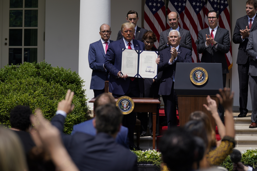 President Trump poses for a photo after signing the Paycheck Protection Program Flexibility Act during a news conference June 5 in the Rose Garden of the White House in Washington.