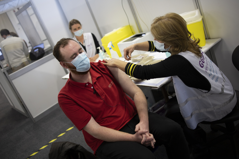 An employee of the Municipal Health Service GGD, right, administers a Pfizer-BioNTech COVID-19 vaccine to a health care worker at a coronavirus vaccination facility in Houten, central Netherlands, last week. Evidence so far suggests that the new mutations will have little, if any, impact on how well the vaccines work, and they do not seem to result in more severe illness.