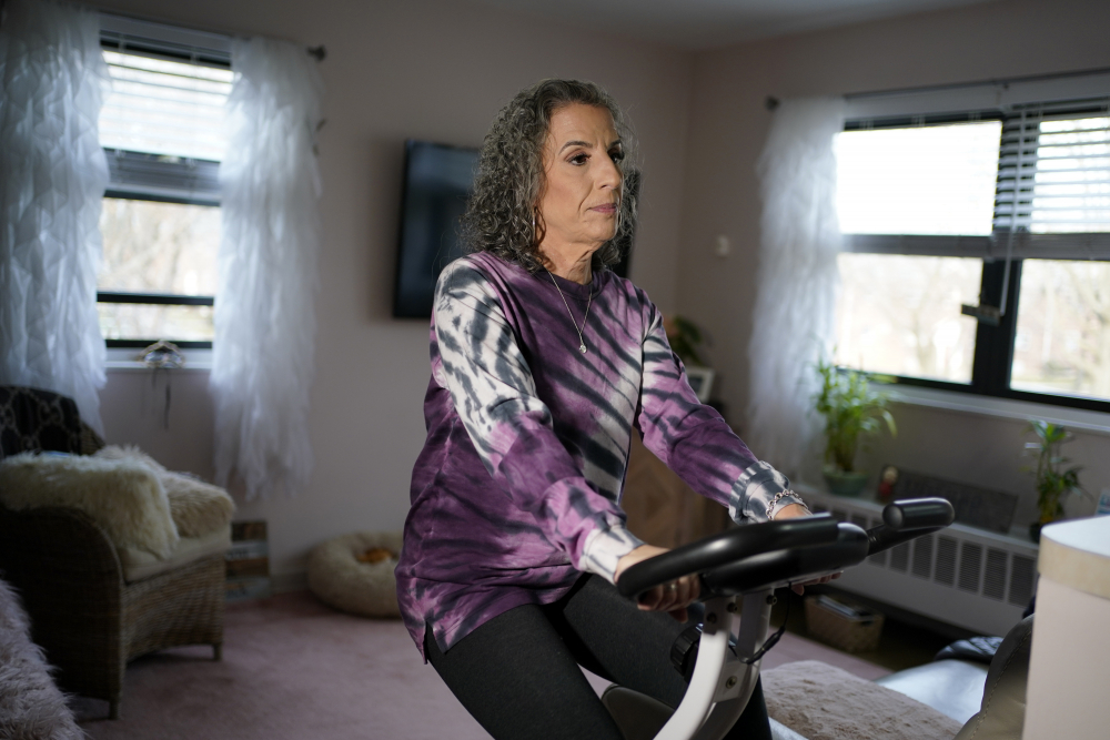 Catherine Busa rides an exercise bike as part of her recovery from COVID-19 at her home in New York. The 54-year-old didn't have any underlying health problems when she caught the virus in March. Eight months later, she's still battling fatigue, muscle weakness and altered senses.