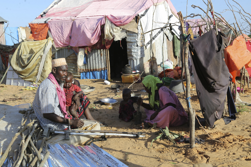 Hassan Mohamed Yusuf, 45, sits with his family at their makeshift shelter at the Dayniile camp in Mogadishu, Somalia on  Dec. 17, 2020. Three of his young children died after having a cough and high fever, but they had no access to coronavirus testing or proper care.