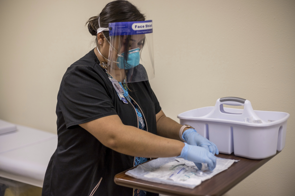 Registered nurse Starla Garcia prepares a coronavirus vaccine in Chinle, Ariz., on Tuesday for someone who enrolled in the COVID-19 vaccine trials on the Navajo Nation and initially received a placebo.