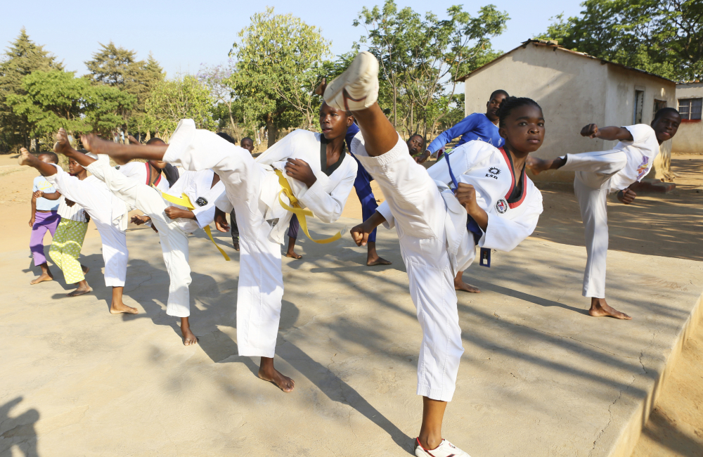 Natsiraishe Maritsa, second right, goes through taekwondo kicking drills during a practice session with young boys and girls in the Epworth settlement in Zimbabwe on Nov. 7, 2020. An estimated 30 percent of girls are married before reaching 18, according to the United Nations Children's Fund.
