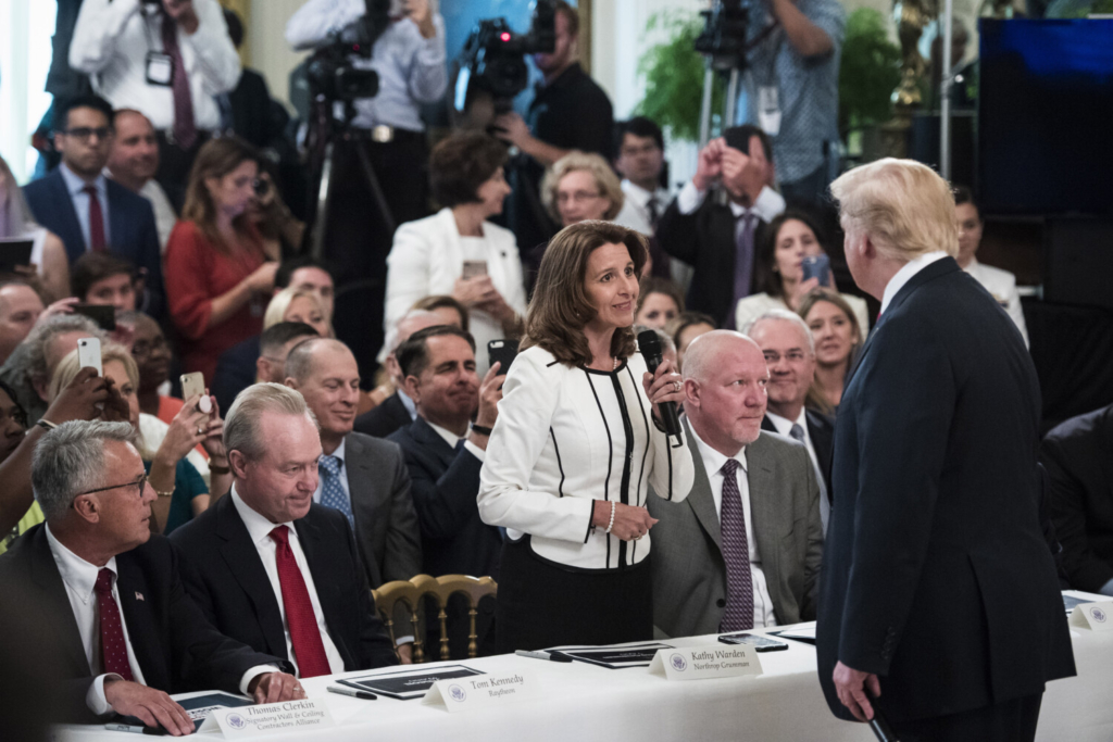 """President Trump talks with Northrop Grumman CEO Kathy Warden during a """"Pledge to America's Workers"""" event in the East Room of the White House in 2018. The company hasn't released a statement explaining the donation halt."""