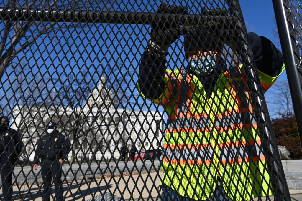 Workers put up fencing outside the U.S. Capitol on Jan. 7, a day after the violent insurrection.