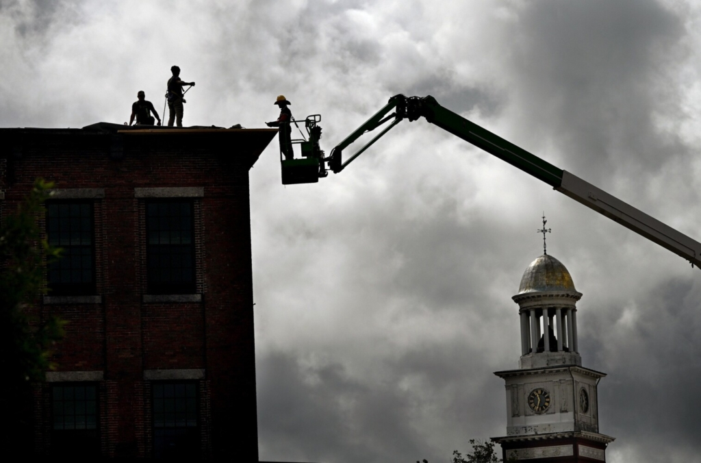 Workers work on the roof at the Lincoln Mill in Biddeford in September. The clock tower of Biddeford City Hall is to the right. A ground breaking ceremony took place in October of 2019 and when completed The Lincoln will be a mixed-use hotel and residential property located in the Lincoln Mill Building.