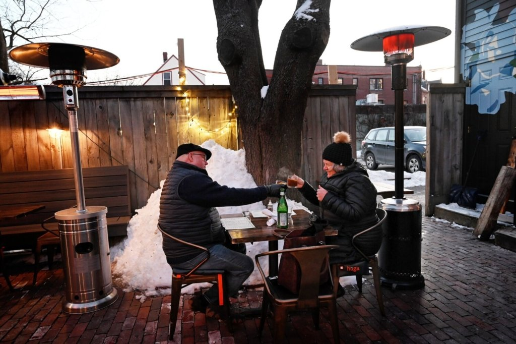 Paul and Elizabeth Piche of Gorham clink glasses as steam rises from Elizabeth's hot toddy. The two were dining under heat lamps at Chaval on a cold February evening.