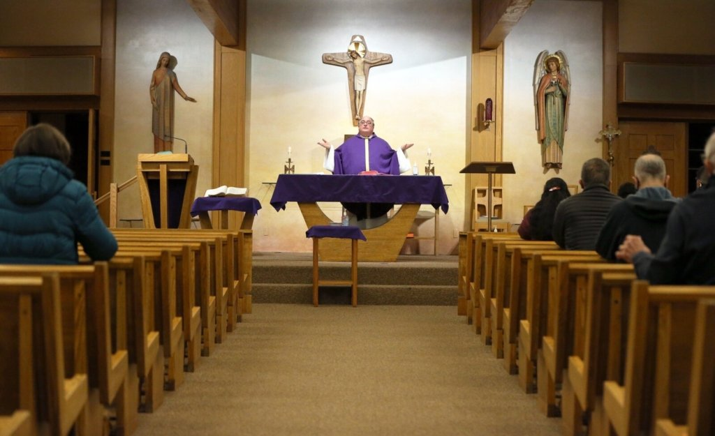 """The Rev. Philip Tracy celebrates Mass at Holy Martyrs Church in Falmouth on Thursday. Bishop Robert Deeley of the Roman Catholic Diocese of Portland called the governor's updated order limiting the number of people in churches """"unacceptable."""""""