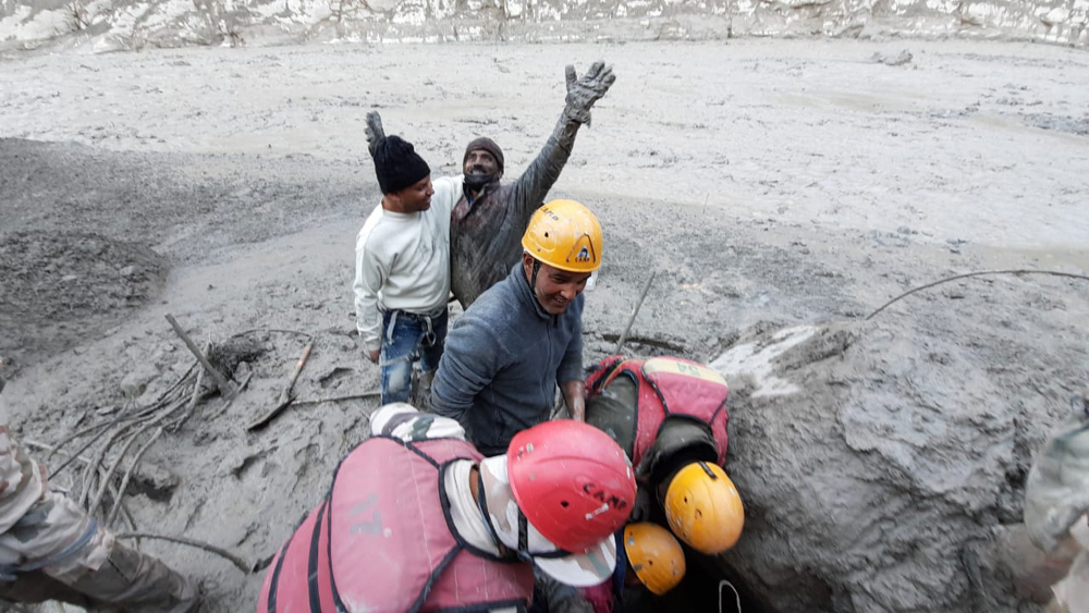 A man reacts after he was pulled out from beneath the ground by ITBP personnel during rescue operations after a portion of Nanda Devi glacier broke off Sunday in Tapovan area of the northern state of Uttarakhand, India.