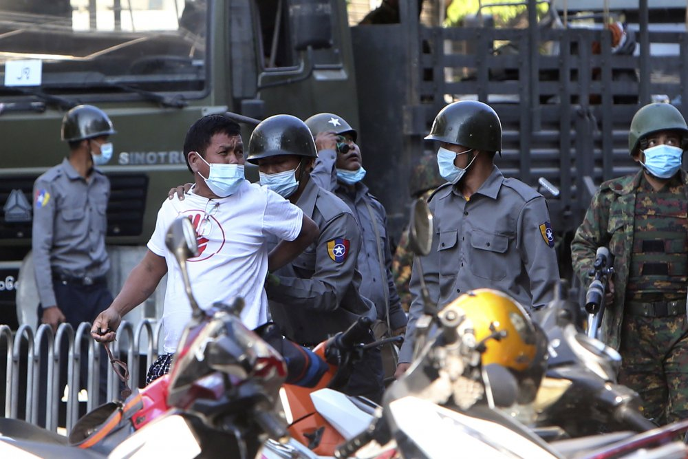 A man is held by police during a crackdown on anti-coup protesters holding a rally in front of the Myanmar Economic Bank in Mandalay, Myanmar on Monday. Soldiers and police attacked protesters with sticks and local media reported that rubber bullets were fired into the crowd. Police also were seen pointing guns toward protesters.