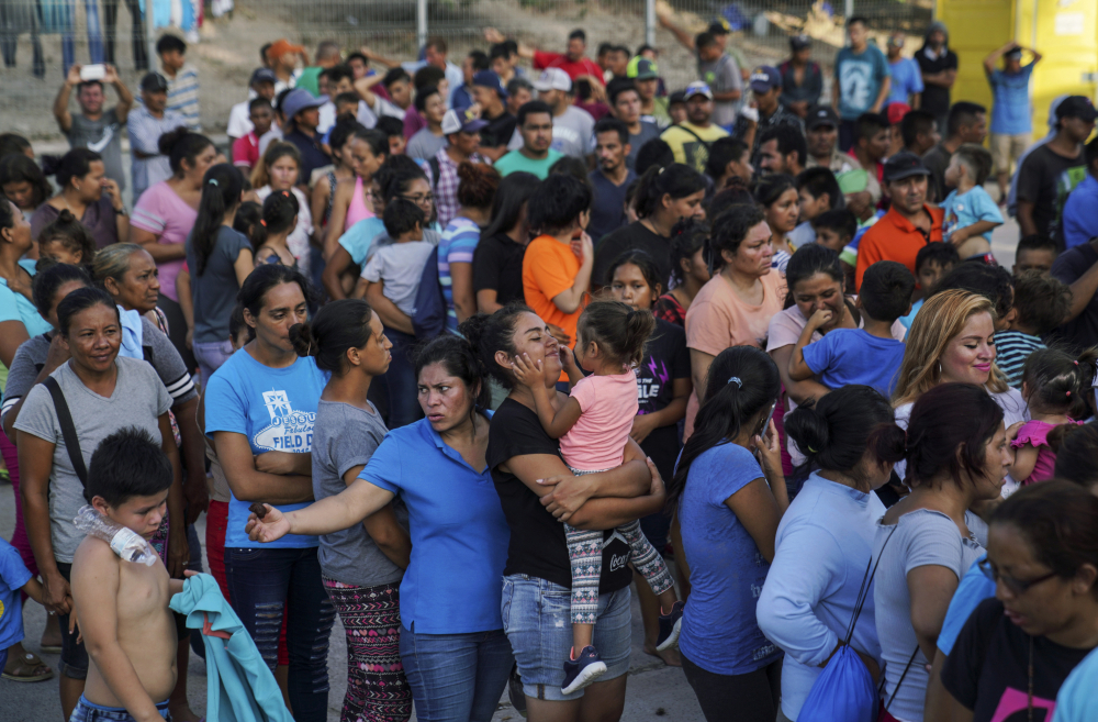 "Migrants, many of whom were returned to Mexico under the Trump administration's ""Remain in Mexico"" policy, wait in line to get a meal in an encampment near the Gateway International Bridge in Matamoros, Mexio on Aug. 30, 2019. The Biden administration on Friday announced plans for tens of thousands of asylum-seekers waiting in Mexico for their next immigration court hearings to be released in the United States while their cases proceed."
