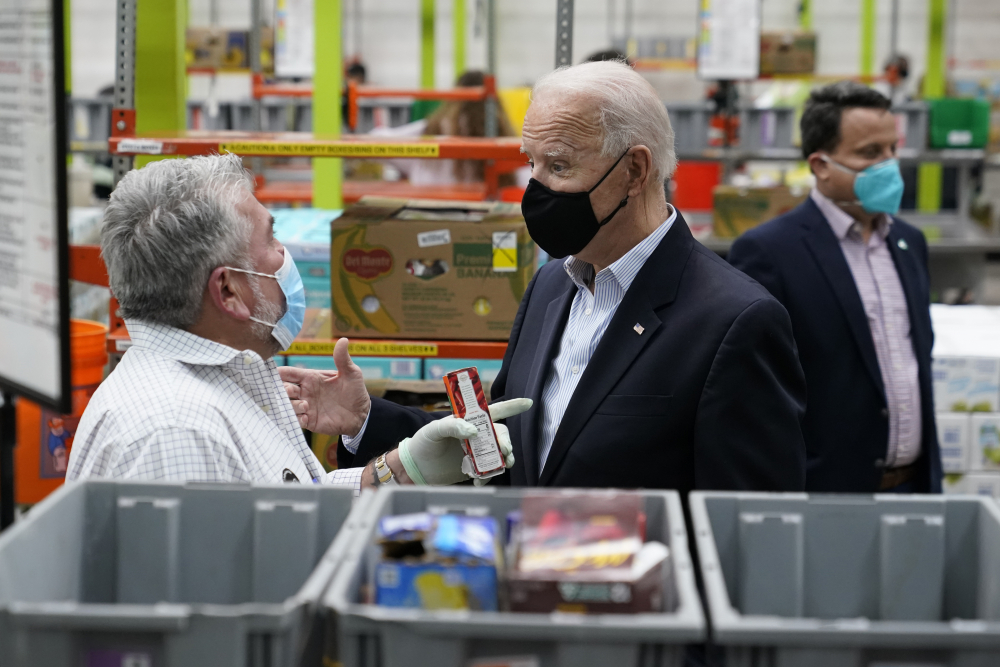 President Biden talks with a volunteer at the Houston Food Bank on Friday in Houston.