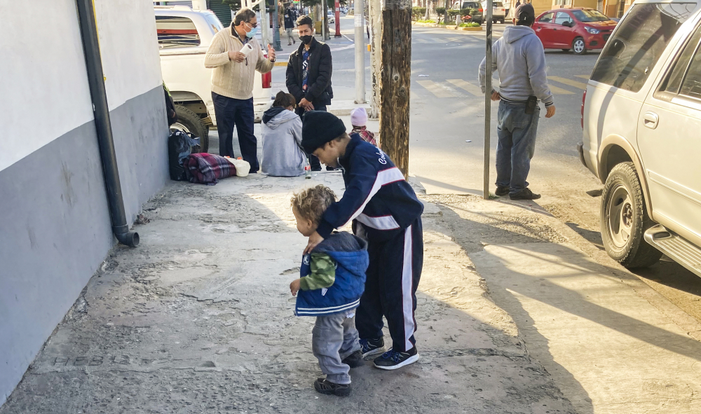 """Honduran boys, whose family is seeking asylum in the U.S., play on the sidewalk in Tijuana, Mexico, on Feb. 8. The Biden administration has rolled back several Trump-era policies, but White House Press Secretary  Jen Psaki said at a recent briefing that """"now is not the time to come and the vast majority of people will be turned away."""""""