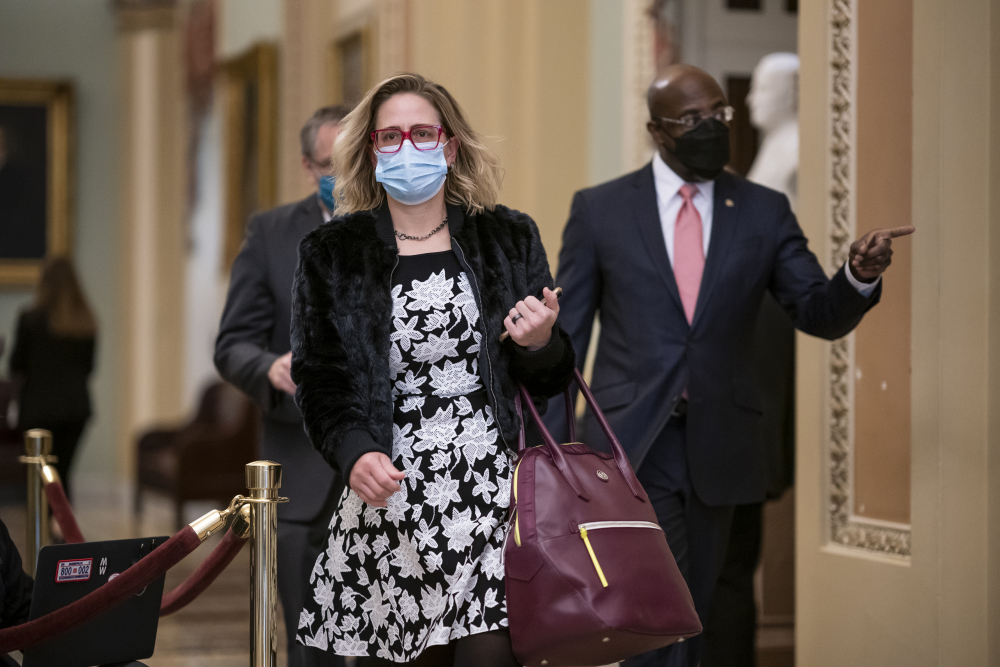 Sen. Kyrsten Sinema, D-Ariz., and Sen. Raphael Warnock, D-Ga., right, arrive as the second impeachment trial of former President Donald Trump starts in the Senate on Feb. 9. Sinema has suggested she may oppose boosting the federal minimum wage in the  relief package.