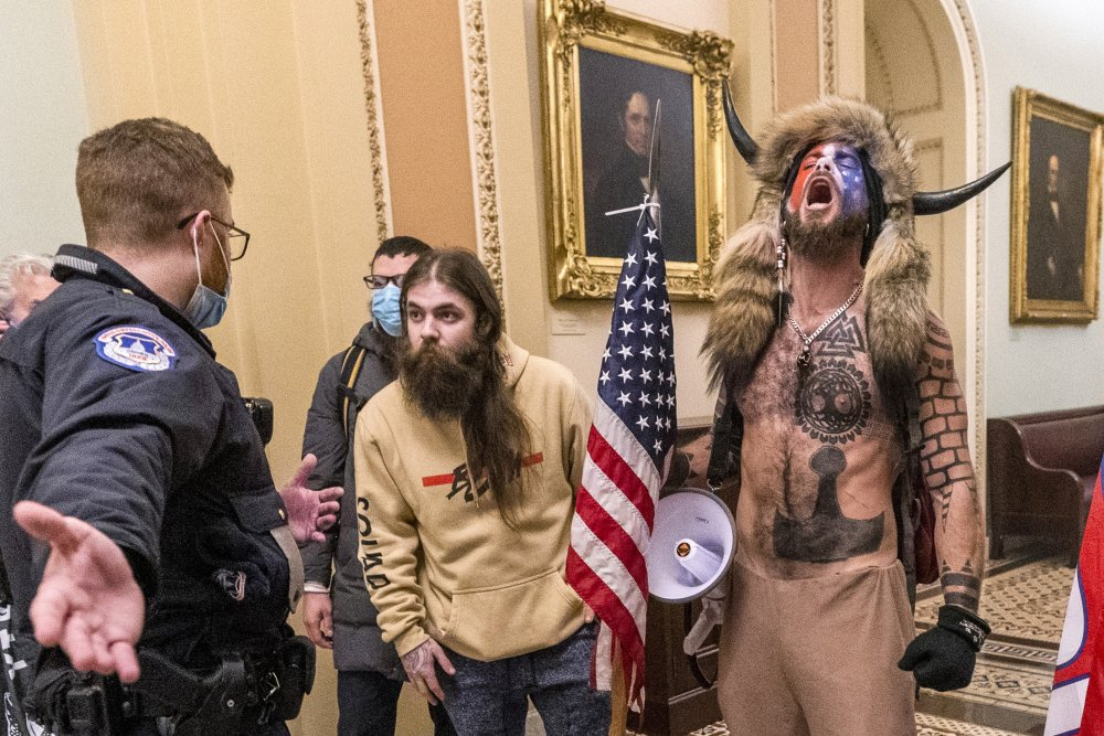 Supporters of President Trump, including Jacob Chansley, right with fur hat, are confronted by U.S. Capitol Police officers outside the Senate Chamber inside the Capitol in Washington during the insurrection on Jan. 6.