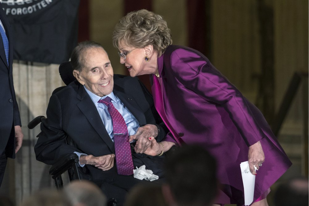 FILE - In this Jan. 17, 2018 file photo, former Senate Majority Leader Bob Dole smiles as he gets a kiss from his wife Elizabeth Dole as he is honored with a Congressional Gold Medal, at the Capitol in Washington. A political icon and 1996 Republican presidential nominee, Dole says he has been diagnosed with stage 4 lung cancer.