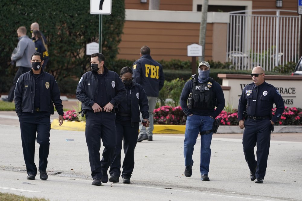 Law enforcement officers walk near the entrance to an apartment complex where a shooting killed or wounded several FBI agents serving an arrest warrant, Tuesday, Feb. 2, in Sunrise, Fla.