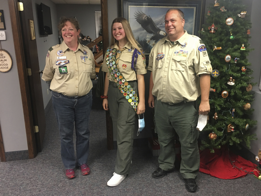 Isabella Tunney, center, with Bev Verweg, her scoutmaster, and Brian Reiners, the scoutmaster of the corresponding linked boy troop, in Edina, Minn.