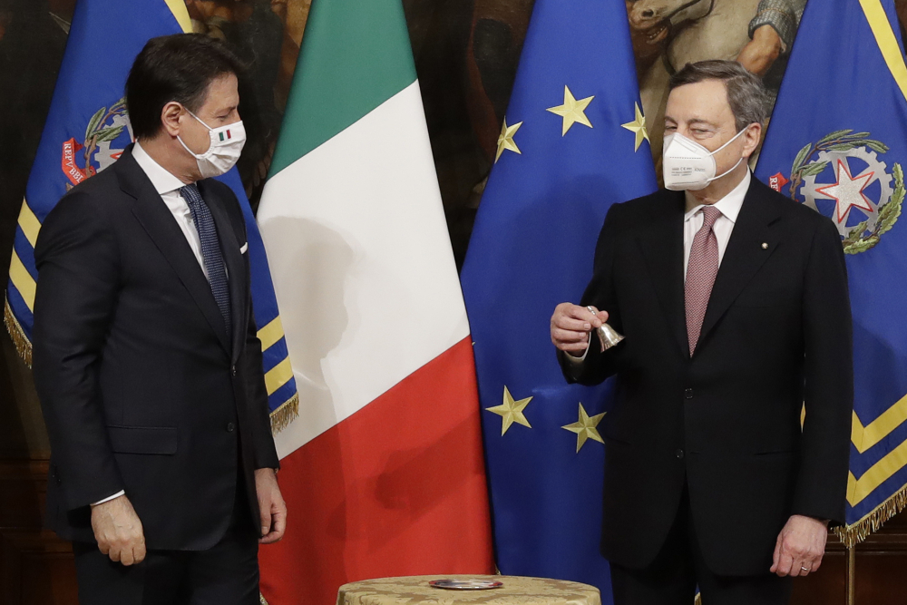 Italian outgoing Premier Giuseppe Conte hands over the Cabinet minister bell to new Premier Mario Draghi during a ceremony at Chigi Palace in Rome on Saturday.