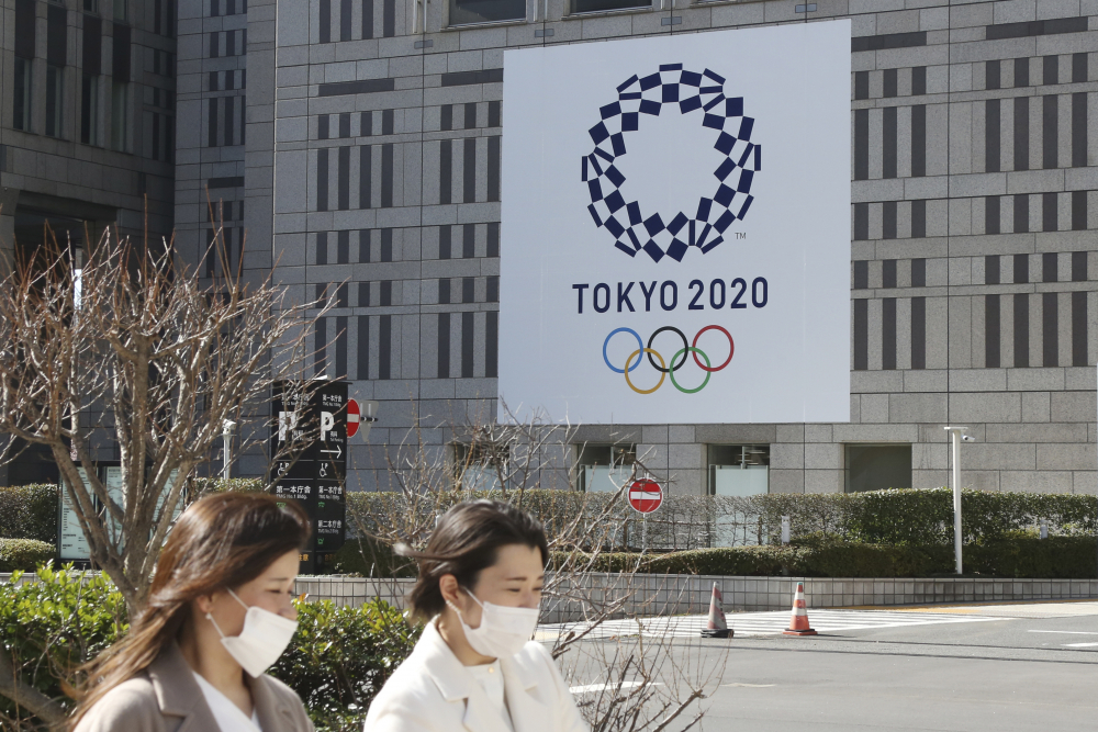 People wearing face masks pass by the logo of the Tokyo Olympics, in Tokyo, Wednesday, Feb. 17. The Olympics are scheduled to open on July 23 but recent polls show about 80% of the Japanese public want the Olympics canceled or postponed.