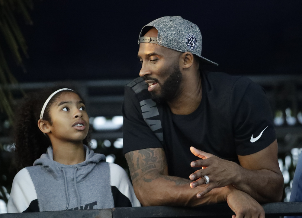Former Los Angeles Laker Kobe Bryant and his daughter Gianna watch the U.S. national championships swimming meet in Irvine, Calif. on July 26, 2018.