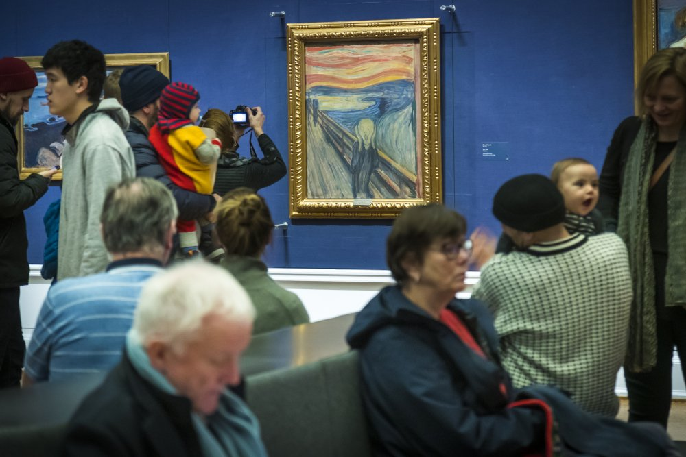 """People look at """"The Scream"""" at the National Gallery in Oslo in 2019. A Norwegian museum says a small, barely visible sentence written on Edvard Munch's 1893 masterpiece was penned by the Norwegian painter himself."""