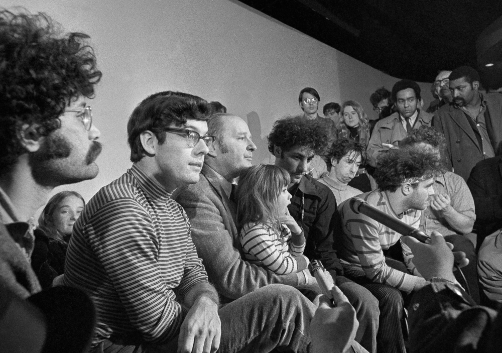 The defendants in the Chicago Seven trial hold a news conference in Chicago in 1970. Left to right, Lee Weiner, Rennie Davis, David Dellinger, Abbie Hoffman, Tom Hayden, (behind Hoffman), Jerry Rubin and John Froines. Dellinger holds his granddaughter, Michelle Burd. Davis has died at age 80.