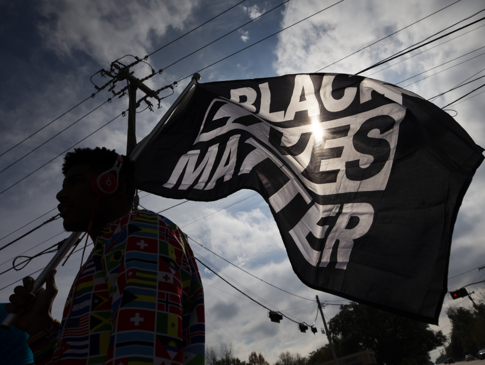 MD Crawford carries a Black Lives Matter flag before a march in La Marque, Texas, in December to protest the shooting of Joshua Feast, 22, by a La Marque police officer. The Black Lives Matter Global Network Foundation is now building infrastructure to catch up to the speed of its funding and plans to use its endowment to become known for more than protests after Black Americans die at the hands of police or vigilantes.