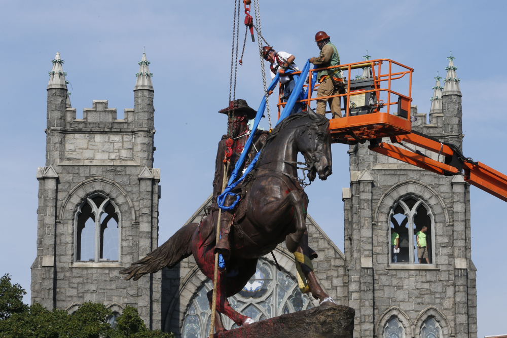 Crews attach straps to the statue Confederate General J.E.B. Stuart on Monument Avenue in Richmond, Va. in July 2020. At least 160 Confederate symbols were taken down or moved from public spaces in 2020.