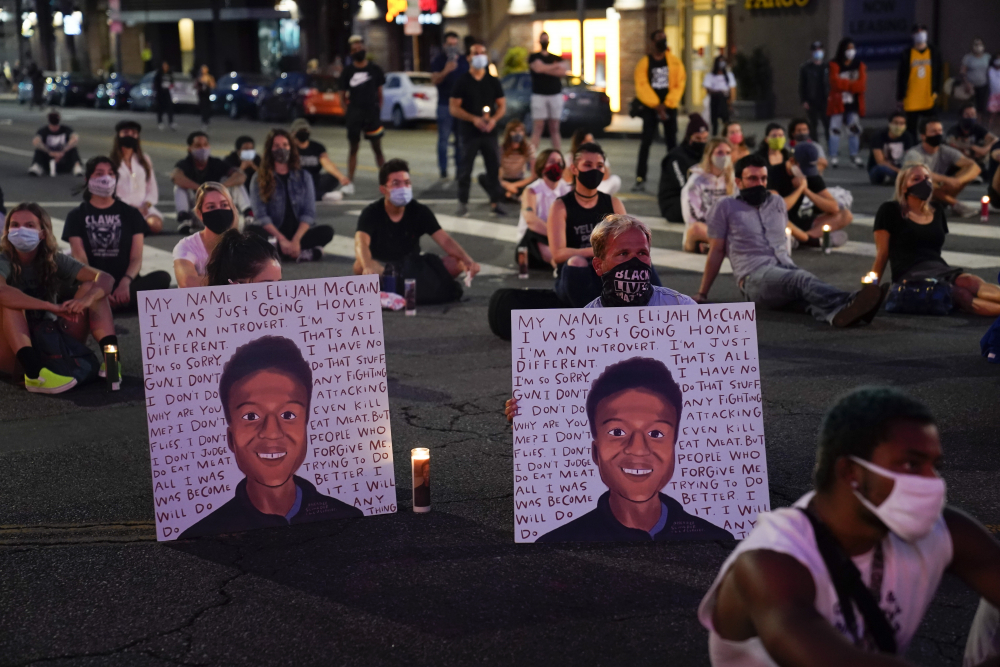 People hold a candlelight vigil for Elijah McClain during a candlelight vigil for McClain on Aug. 24, 2020, outside the Laugh Factory in Los Angeles.